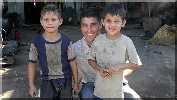 Vinicio with 2 young boys after teaching them how to change a tire.