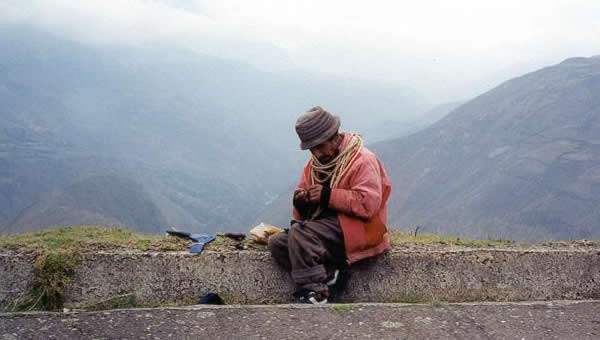 A man rests beside a mountain road in Ecuador.