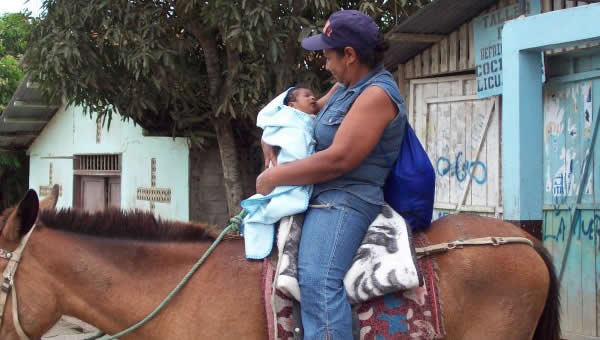 A mother carries her baby on a horse in Ecuador.